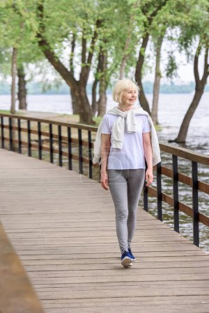Photo for Smiling senior woman walking on wooden path in park - Royalty Free Image