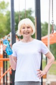 smiling senior sportswoman with water in sport bottle standing on sports ground