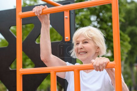 senior sportswoman with grey hair training on sports ground