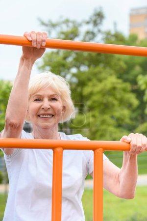 smiling senior sportswoman exercising on sports ground
