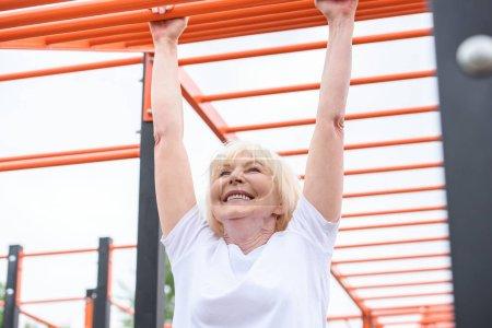 cheerful senior woman exercising on sports ground