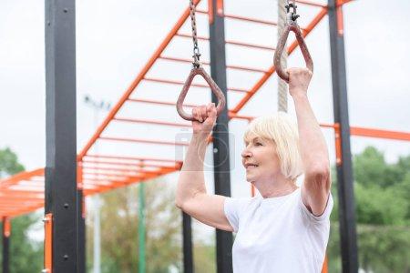 senior sportswoman training on rings on sports ground