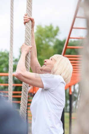 elderly woman exercising with rope on sports ground