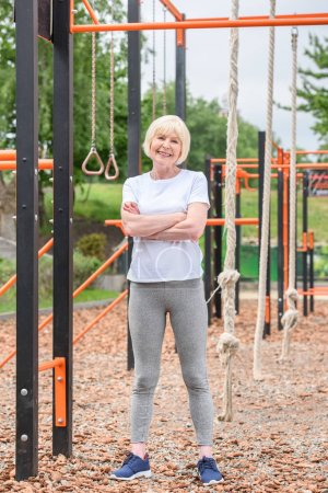 happy elderly sportswoman with crossed arms standing on sports ground