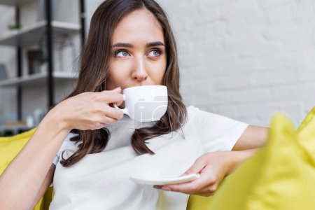 Photo for Beautiful pensive brunette girl drinking coffee and looking away at home - Royalty Free Image