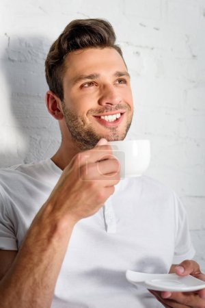 handsome smiling young man drinking coffee at morning at home