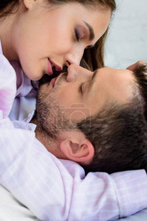 close-up view of beautiful young couple in love kissing at home