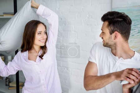 young smiling couple having pillow fight in bedroom