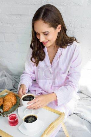 Foto de Atractiva mujer feliz rosa pijama desayunando en bandeja en la mañana - Imagen libre de derechos