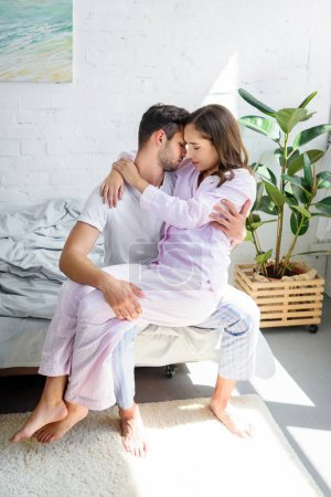young tender woman sitting on knees of her boyfriend and hugging him on bed