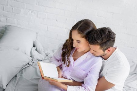 Photo pour Jeune couple étreindre et lecture livre ensemble au lit - image libre de droit