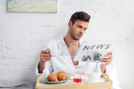 handsome man in bathrobe reading newspaper during breakfast with coffee