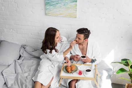 Photo for Beautiful young couple in bathrobes having breakfast in bed together - Royalty Free Image