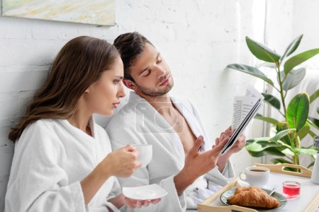 young couple with coffee for breakfast reading newspaper together