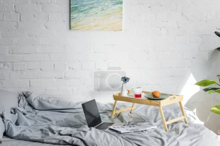 laptop and breakfast with croissant and coffee on tray in bedroom with painting on wall