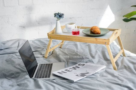 laptop with blank screen and breakfast with croissant and coffee on tray on bed in morning