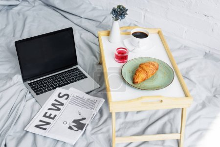 laptop, newspaper and breakfast with croissant and coffee on tray on bed in morning