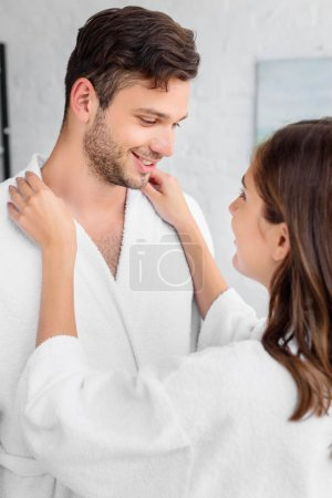 happy couple in white bathrobes standing together in morning