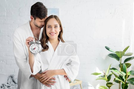 couple in white bathrobes embracing and holding alarm clock in morning