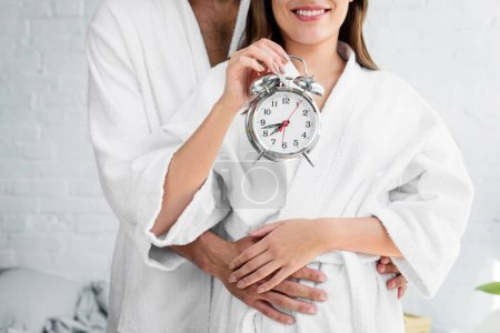 cropped view of couple in white bathrobes holding alarm clock and standing in bedroom