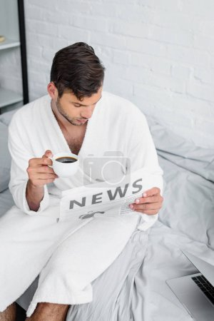 young man in bathrobe sitting on bed, reading newspaper and holding cup of coffee