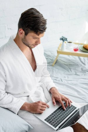young man in bathrobe sitting on bed and using laptop