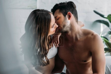 Photo for Sensual couple kissing on bed at home in morning - Royalty Free Image