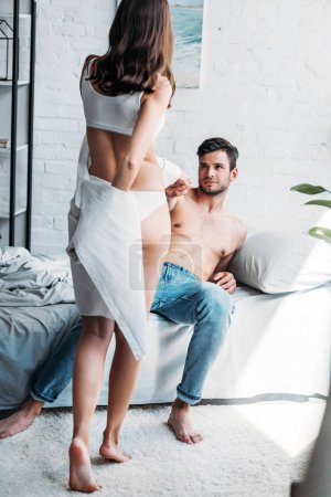 shirtless boyfriend lying on bed and pulling girlfriend in underwear