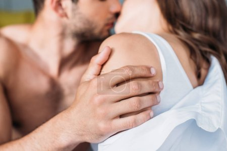 Photo for Cropped image of heterosexual couple hugging and kissing at home - Royalty Free Image