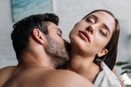 boyfriend kissing sensual girlfriends neck in bedroom in morning
