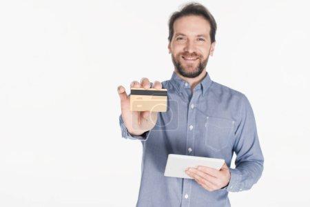 Photo pour Portrait d'homme souriant avec tablette numérique montrant carte de crédit isolée sur blanc - image libre de droit