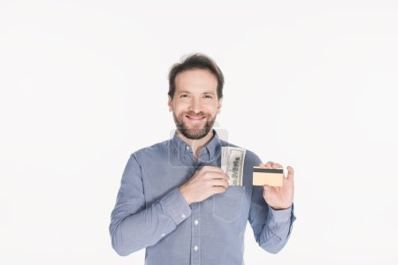 portrait of smiling bearded man with dollar banknotes in pocket showing credit card in hand isolated on white