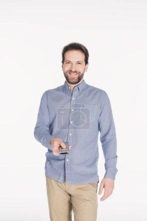 Photo pour Portrait d'un homme souriant avec télécommande à main isolé sur blanc - image libre de droit