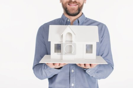 cropped shot of bearded man holding house model in hands isolated on white