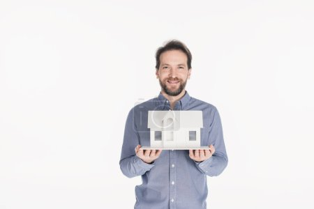 portrait of cheerful bearded man holding house model in hands isolated on white