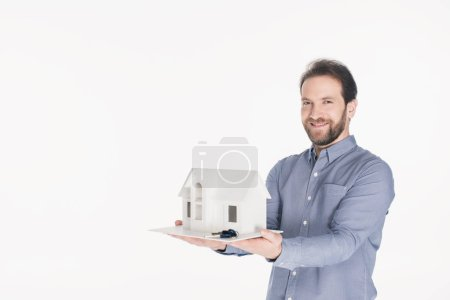 portrait of smiling bearded man holding house model and keys in hands isolated on white