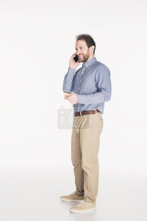 side view of bearded man with credit card in hand talking on smartphone isolated on white