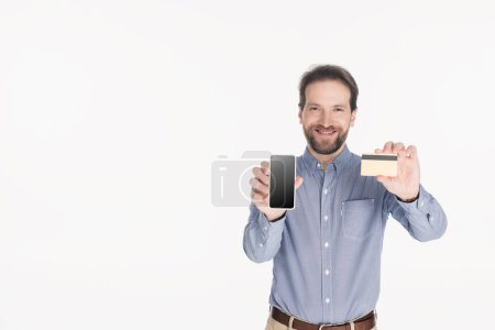 portrait of smiling bearded man showing smartphone with blank screen and credit card in hands isolated on white