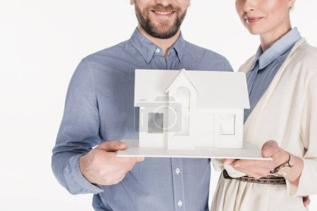 partial view of smiling married couple with house model isolated on white