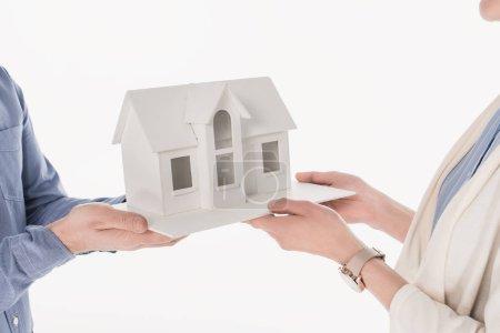 cropped shot of couple holding house model isolated on white