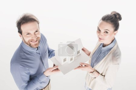 high angle view of married couple holding house model together isolated on white
