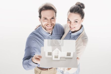 high angle view of smiling couple holding house model together isolated on white