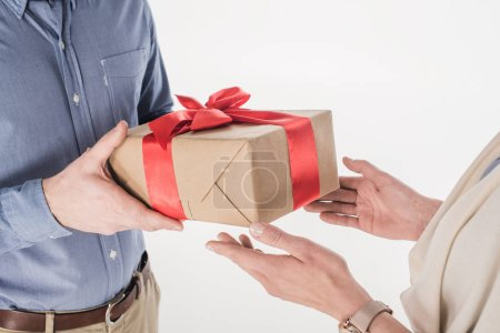 side view of man presenting wrapped gift to woman isolated on white
