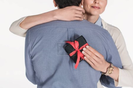 partial view of woman with wrapped present in hand hugging husband isolated on white