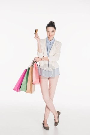 Photo for Smiling stylish woman with shopping bags and credit card in hands isolated on white - Royalty Free Image