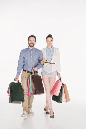 smiling couple with shopping bags and credit card isolated on white