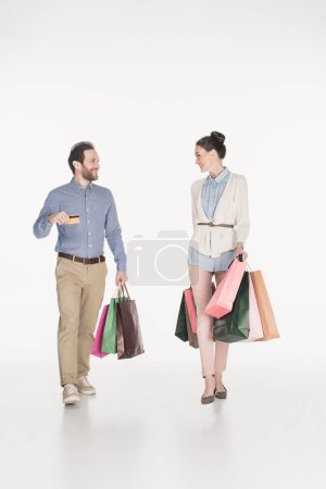 couple with shopping bags and credit card looking at each other isolated on white