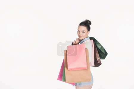 Photo for Side view of stylish woman with shopping bags looking at camera isolated on white - Royalty Free Image