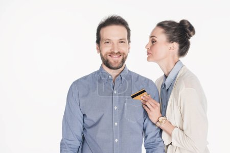 portrait of woman taking credit card from husbands pocket isolated on white