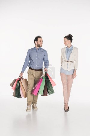 Photo for Woman looking at smiling husband carrying shopping bags isolated on white - Royalty Free Image